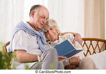 Elderly man embracing his wife and reading her a book