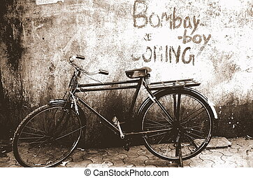 Bombay Boy Coming - A cycle beneath a wall, written on the...