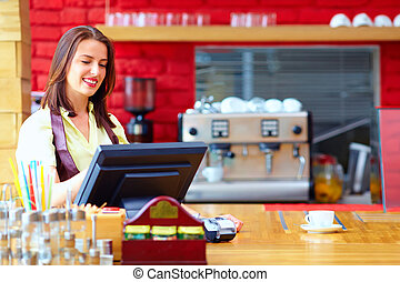 young female cashier operating at the cash desk in cafe
