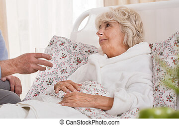 Ill woman lying in bed - Ill senior woman lying in bed and...