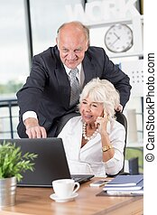 Mature businessman with his wife in the office