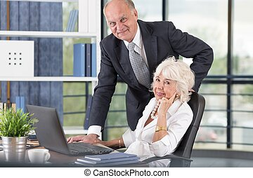 Senior business people at work in the office with laptop