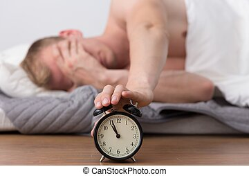 Annoying alarm clock - Young man is trying to turn off an...