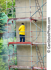 Man cleaning wall Scaffolding, construction site in progress...