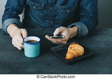 denim coffee - young hipster checking his mobile phone while...
