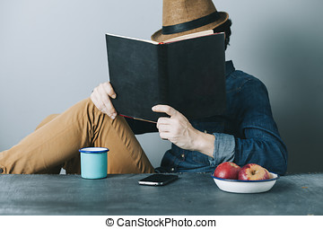 denim book - young hipster man reading a book and relaxing