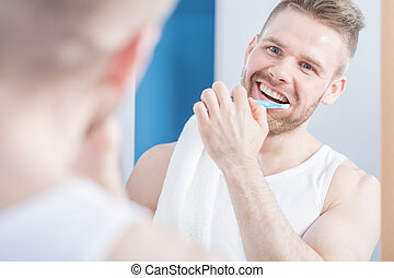 Attractive guy brushing his teeth - Attractive guy with...