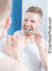 Unshaved man brushing his teeth before meeting