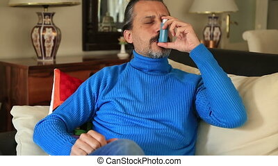 Mid adult man using asthma inhaler - Man seated on a sofa...