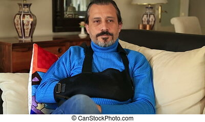 Painful man with a broken arm wearing arm brace sitting on...