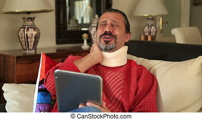 Painful man with neck brace sitting on sofa and using...