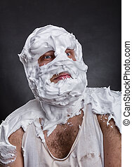 Bizarre man with face completely in shaving foam thinks over...