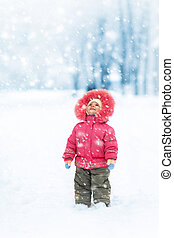 Cute girl winter portrait. Looking at falling snowflakes