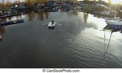 camera flying over the rowing boat - man in a rowing boat...