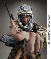Serious middle eastern man with AK-47 pointing to you