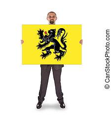 Smiling businessman holding a big card, flag of Flanders -...