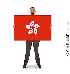 Smiling businessman holding a big card, flag of Hong Kong,...