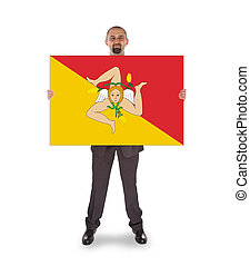 Smiling businessman holding a big card, flag of Sicily,...