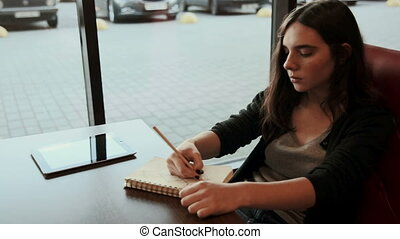 Teenage student makes sketches in notebook in cafe - Teenage...