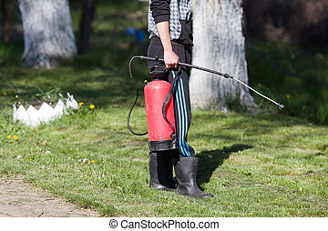 Young man holding spray for gardening - Close up of man...