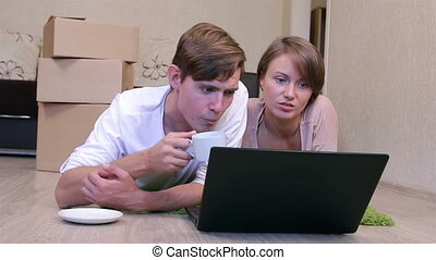 Young couple with a laptop - Internet surfing on the floor...