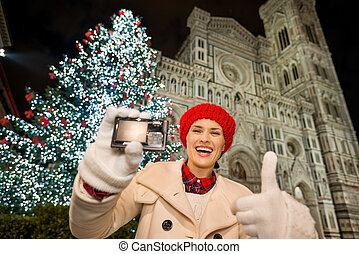 Woman showing camera and thumbs up in Christmas Florence,...