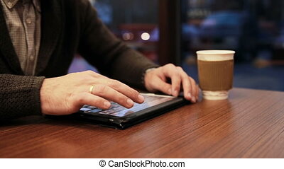 man hands using tablet touchscreen in cafe - Close up man...