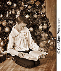 Boy under on Christmas tree read book - Boy under Christmas...