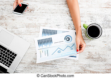 Business Analytics - A young woman holding a analytical...
