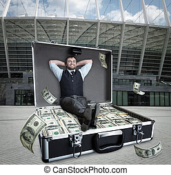 Happy businessman sits in the case full of dollars outdoors
