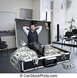 Happy businessman sits in the case full of dollars in the...