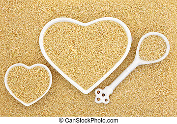 Couscous in heart shaped bowls and porcelain spoon forming...