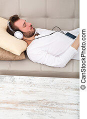 Young man listening to music on the sofa