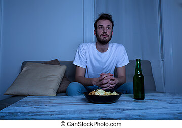 Young man watching TV at nighttime with chips and beer - A...