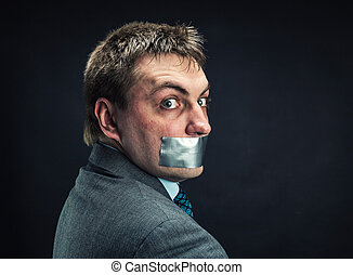 Man with mouth covered by masking tape ,studio shoot