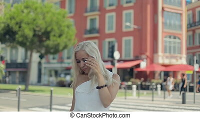 Happy young blond woman in white dress posing on a background of pink houses of Nice