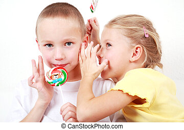 Kids whispering - Girl whispering a secret to a boy