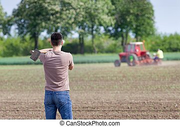 Farmer with hoe - Rear view of attractive farmer carrying...