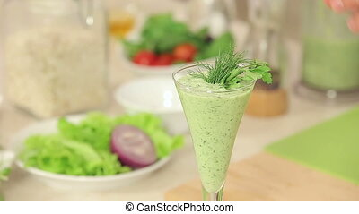 Chef is Decorating a Glass of Green Vegetable Smoothies with Herbs and Red Chili Pepper
