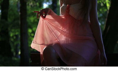 Girl in a Pink Dress Sitting on the Bench on a Sunny Summer...