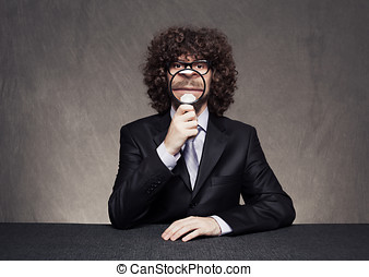 business magnify - serious businessman holding a magnifying...