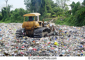 Garbage Landfill - Bulldozer spreads garbage in a landfill;...