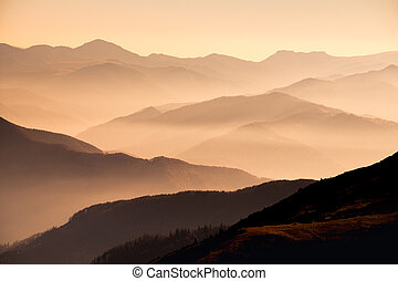 Landscape view of misty mountain hills at sunset with...