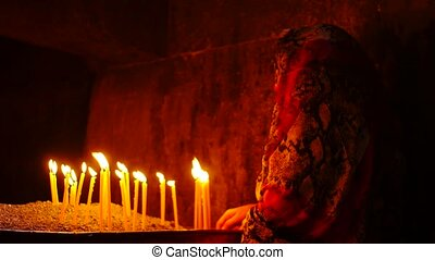 Ancient and Mysterious Woman Lighting Candles