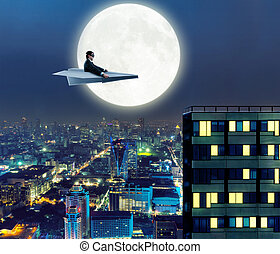 Man on paper airplane above the city - Businessman on paper...