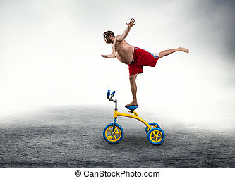Man standing on a small bicycle - Nerdy man standing on a...