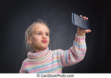 Little girl doing selfie - Little glamour girl makes face...