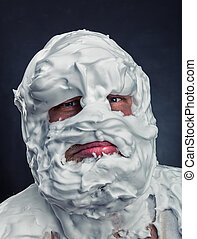 Crazy man with face completely in shaving foam thinks