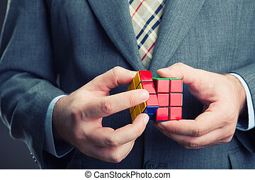Businessman holding rubik cube in his hands - Rubik cube in...