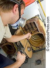 Repair man servicing big gas boiler